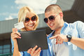 Online shopping young couple using a digital tablet for outdoors on a sunny day Stock Photos