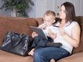Online shopping with young son attractive casual mother from home toddler on her lap holding credit card using wireless mobile Royalty Free Stock Images