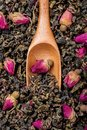 Oolong tea with delicate rose buds top view of wooden spoon on roses Stock Photography