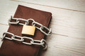 Open bible chained with lock on wooden table Stock Image