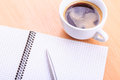 Open blank note book with coffee cup on table and a pen wood Stock Image