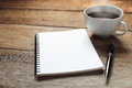 Open a blank white notebook, pen and cup of coffee Royalty Free Stock Photo