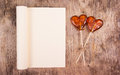 Open book with blank page and two lollipop in the shape of a heart on an old wooden table
