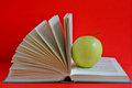Open book and fresh apple red background Royalty Free Stock Photo