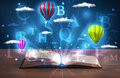 Open book with glowing fantasy abstract clouds and balloons on wood deck Stock Photos