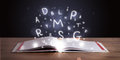 Open book with glowing letters flying