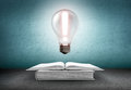 Open book and glowing light bulb with exclamation sign over it. Knowledge, education concept Royalty Free Stock Photo