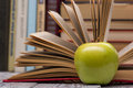 Open book, hardback books and green apple on Royalty Free Stock Photo