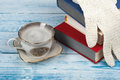 Open book, hardback books on wooden table, cup and white gloves knitted crochet Back to school. Copy space for text. Royalty Free Stock Photo