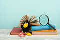 Open book, hardback colorful books on wooden table. Magnifier, toy crow. Back to school. Copy space for text. Education business c Royalty Free Stock Photo