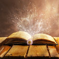 Open book magic on wooden background Royalty Free Stock Photography