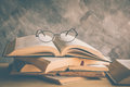 open book with reading glasses in the bookshelf Royalty Free Stock Photo