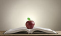 Open book on a wooden Desk with a red Apple Royalty Free Stock Photo