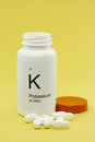 Open bottle of potassium vitamins an white white vitamin pills against a yellow background Stock Photo