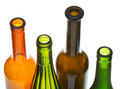 Open bottlenecks of colored wine bottles close up four isolated on white background Royalty Free Stock Photography