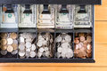 Open cash register drawer on wooden table Royalty Free Stock Photo