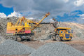 Open cast vine big yellow excavator extracting iron ore and loading in heavy truck in mine Stock Photography