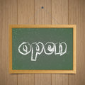 Open. Chalk board with wooden frame on a wooden background