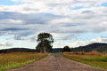 Open country road ahead with clouds & fields Royalty Free Stock Photos
