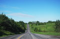 Open Country Road lined by trees and greenery Royalty Free Stock Photo