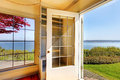 Open door from the living room to the back yard with water view. Royalty Free Stock Photo