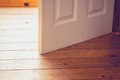 Open door on sunny day in a room with wood floor Royalty Free Stock Images