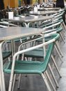 Open empty street cafe, tables and chairs with metal frame and wicker furniture, selective focus and close-up, vertical frame Royalty Free Stock Photo