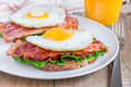 Open face sandwich with egg bacon tomato and lettuce closeup Royalty Free Stock Image