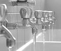 Open faucets with water flowing in the bath changing rooms many Royalty Free Stock Photos