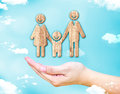Open female hand with Happy family wood icon with blue sky and c Royalty Free Stock Photo