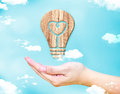 Open female hand with Heart in lightbulb wood icon with blue sky Royalty Free Stock Photo