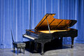Open grand piano on stage with blue velvet cutain ebonised and stool standing in front of curtains ready for a musical recital or Stock Images