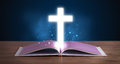 Open holy bible with glowing cross in the middle