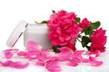 Open jar with the cosmetic cream and rose petals isolated on white Royalty Free Stock Photography