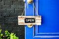 Open label hanging on blue door in garden Royalty Free Stock Photo