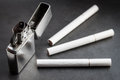 Open metal lighter and three cigarettes. Royalty Free Stock Photo