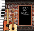 Open mic night guitars and keyboard against brick wall background and written on blackboard Royalty Free Stock Image