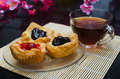 Open mini pies with berries jams and cup of tea on wooden plate Royalty Free Stock Photo