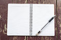 Open Notebook and black pen on old dirty wooden background Royalty Free Stock Photo