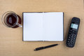 Open notebook and black phone on wooden texture a cup of tea an a ballpoint pen a imitating an office desk Stock Image
