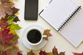 Open notebook, mobile phone and cup of coffee, framed with autumn leaves on white background. Flat lay. Top view. Empty