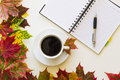 Open notebook, pen and cup of coffee, framed with autumn leaves on white background. Flat lay. Top view. Empty copy