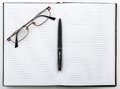 Open notebook with a pen and glasses Royalty Free Stock Photo