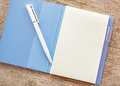 An open notebook and white pen on wood background wooden Royalty Free Stock Image