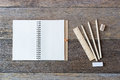 Open notebook on wooden background with pencils and ruler. Royalty Free Stock Photo