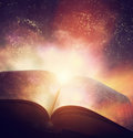 Open old book merged with magic galaxy sky, stars. Literature, h Royalty Free Stock Photo