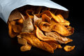 Open packet of fried parsnip and carrot chips on black Stock Photo