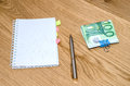 Open daily planner with ball pen one hundred euro banknotes on wooden table background Stock Photos