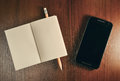 Open pocket book, pencil and cell phone on wooden table Royalty Free Stock Photo