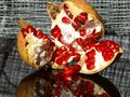 Open pomegranate with red beads on wire netting Royalty Free Stock Photo